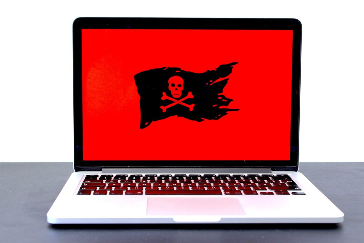 Image of a black and red skull on the screen of an open laptop